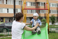 Mother holding child on slide Stock Photography
