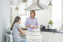 Mother holding coffee cup while looking at daughter studying in kitchen Stock Image