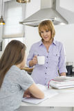 Mother holding coffee cup while looking at girl studying in kitchen Stock Image