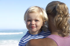 Mother holding daughter (2-4) on beach, smiling, close-up Royalty Free Stock Image
