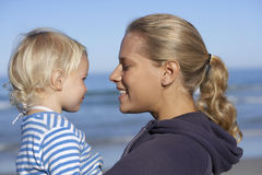 Mother holding daughter (2-4) on beach, smiling, close-up, profile Stock Images