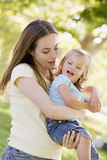 Mother holding daughter outdoors Stock Photography
