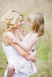 Mother holding daughter outdoors smiling Stock Photo