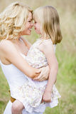 Mother holding daughter outdoors smiling Royalty Free Stock Image