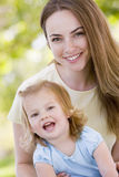 Mother holding daughter outdoors smiling Stock Photography