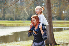 Mother holding daughter in shoulders in a lake Stock Images