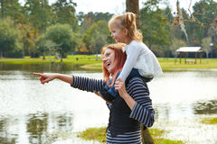Mother holding daughter in shoulders in a lake Royalty Free Stock Images