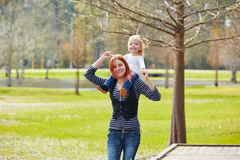 Mother holding daughter in shoulders in a lake Stock Photo