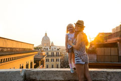 Mother holding daughter standing on ledge at sunset in Rome Royalty Free Stock Photos