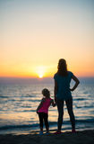 Mother holding daughters hand at sunset looking out to sea Stock Photo