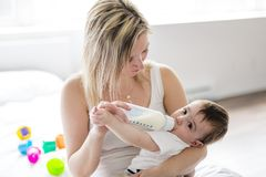 Mother holding and feeding baby from bottle Royalty Free Stock Image