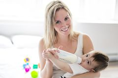 Mother holding and feeding baby from bottle Stock Photos