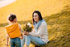 Mother holding flowers, with daughter standing over her on a grassy lawn stock photos
