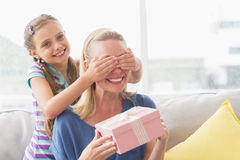 Mother holding gift with daughter covering her eyes Royalty Free Stock Photos