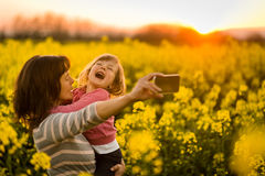Mother holding girl child in arms, clicking selfie. Royalty Free Stock Images