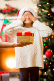 Mother holding on hand Christmas gift and giving to daughter Royalty Free Stock Photo
