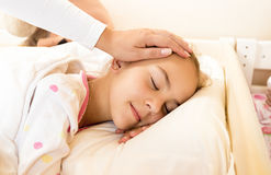 Mother holding hand on daughters head at bed Stock Photo