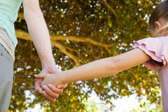 Mother holding a hand of her daughter outdoors Royalty Free Stock Photos