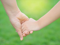 Mother holding a hand of her kid. In spring day outdoors with green field background Stock Image