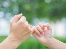 Mother holding a hand of her kid in spring day. Outdoors with green field background Stock Photo
