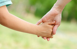 Mother holding a hand of her son Stock Photo