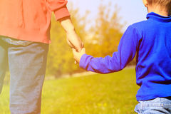 Mother holding hand of her son outdoors. Parenting concept Royalty Free Stock Images