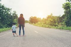 Mother holding a hand of his son in summer day walking on the st. Reet Royalty Free Stock Photo