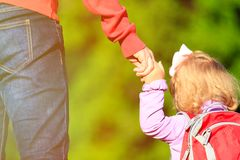 Mother holding hand of little daughter outdoors Stock Photos