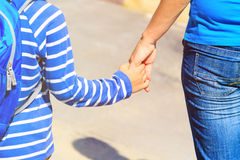 Mother holding hand of little son with backpack, back to school Royalty Free Stock Photos