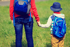 Mother holding hand of little son with backpack Stock Images