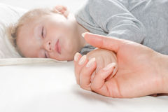 Mother holding by the hand the sleeping baby Stock Photo