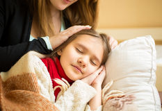 Mother holding hand on sleeping daughters head Royalty Free Stock Images