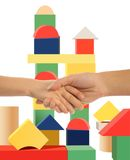 Mother holding hand of son, toy tower background Royalty Free Stock Photography