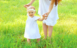 Mother holding hands baby walking together Stock Photography