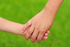 Mother holding hands with child Stock Photos