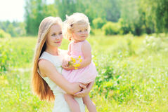 Mother holding on hands child with flowers in summer Royalty Free Stock Photography