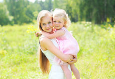 Mother holding on hands child hugging in summer Royalty Free Stock Image