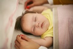 Mother holding hands of her dreaming baby. royalty free stock image