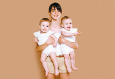 Mother holding on the hands twins baby. On background Royalty Free Stock Photography