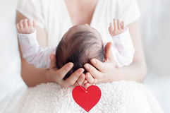 Mother holding head of her newborn baby in hands. Happy family c Stock Image