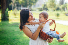 Mother holding her baby in basket outdoor stock images