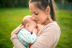 Mother holding her baby daughter, outside in spring nature Stock Images