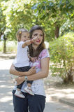 Mother holding her baby girl in park Stock Photo
