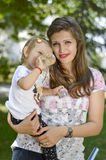 Mother holding her baby girl in park royalty free stock photos