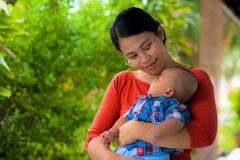 A mother holding her baby with love. A young mother holding her baby in her arms and staring at her baby with love Royalty Free Stock Image