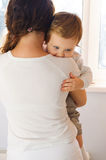 Mother holding her baby near window Stock Photography