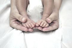 Mother holding her baby's feet. Baby feet in his mother's hand Stock Photos