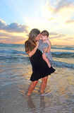 Mother holding her baby. At the sea at sunset Stock Images