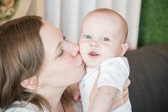 Mother holding her baby son, kissing. Mother holding her baby son, close up family portrait Stock Image