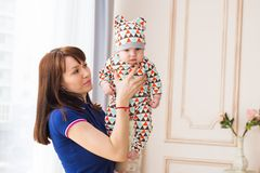 Mother holding her baby son in the room. Young mother holding baby son in the room Stock Images